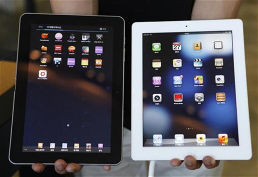 Employee holds up a Samsung Electronics' Galaxy Tab tablet computer and an Apple iPad as he poses at a store in Seoul