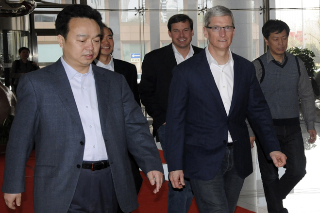 Apple CEO Tim Cook walks with employees as he arrives at the headquarters of China Telecom in Beijing